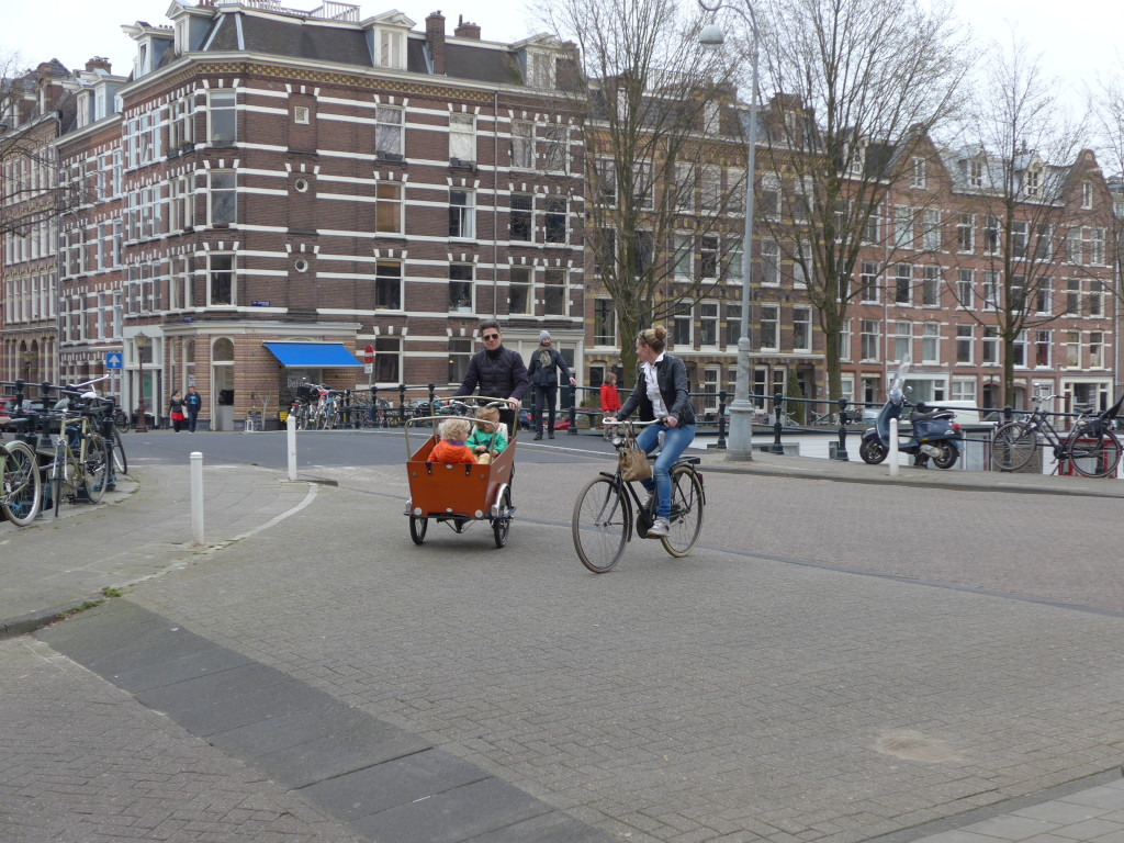 Photo of kids in cargo bike at a junction in Amsterdam