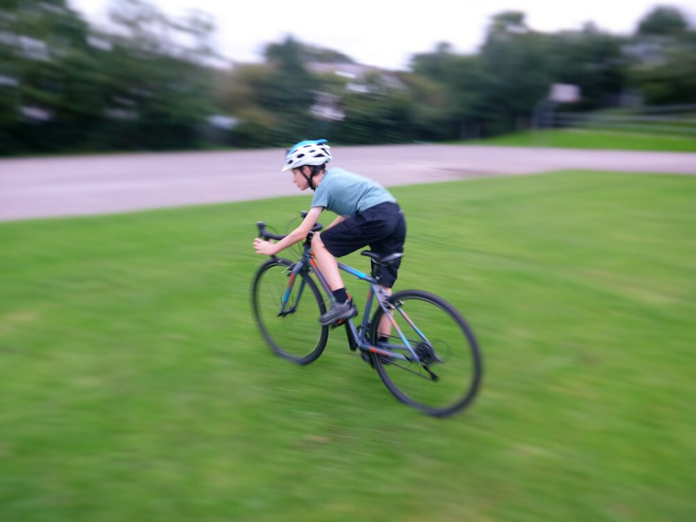 best bike for my child - Cuda CP700R kids road / cyclocross bike in action shot of cyclocross tyres on grass