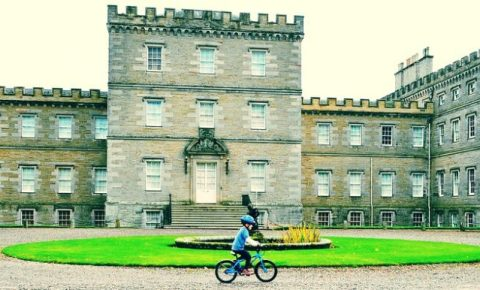 Young boy cycling in front of Mellerstain House
