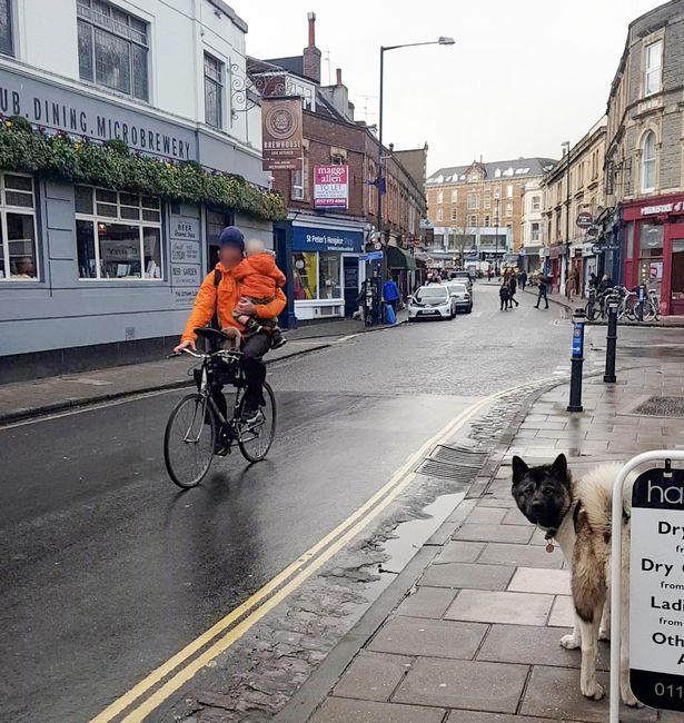 Man on bike holding child in Bristol