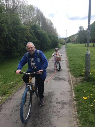 Using a tow rope to tow your child behind your bike is good on the flat or going up hill, but you must remember to unhook it when you go downhill