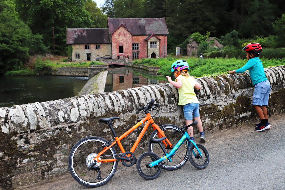 Islabikes kids looking over wall at Mill