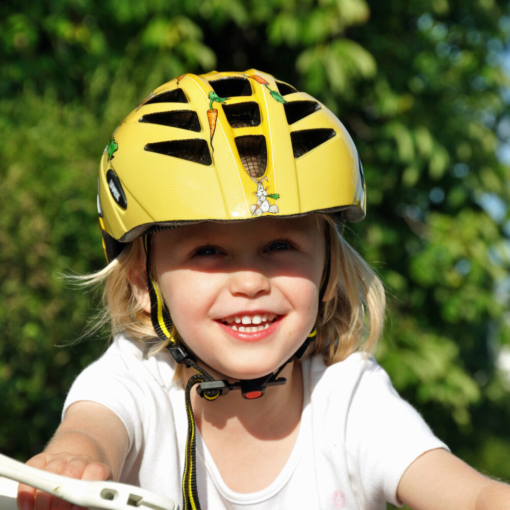 Smiling young girl in yellow cycle helmet?